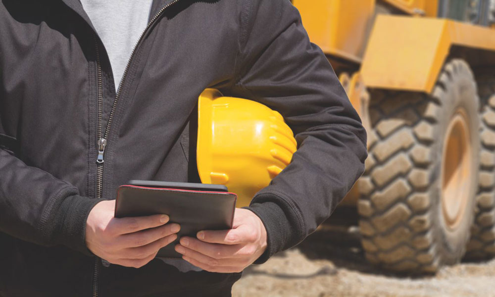Hard hat, tablet and bulldozer
